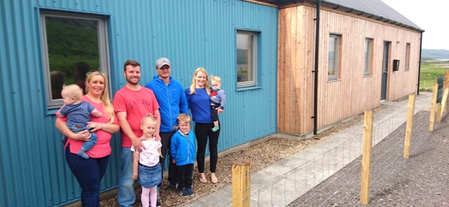 Families standing outside newly built homes